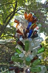 Click to enlarge image  - Bud Quigley's Bottles - Mrs. Quigley put her husbands bottle collection to good use with 14 bottle trees.